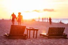 Folk som lämnar stranden på solnedgången Arkivbild