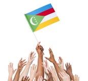 Folk som når för flaggan av Comoros Arkivfoton