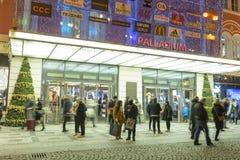 Folk som in och ut kommer från den stora dekorerade köpcentrumpalladiumen i Prague på republikfyrkanten Arkivfoto