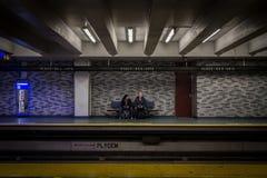 Folk som på plats väntar på för des-konster för gångtunnel en plattform för station, grön linje som sitter på en bänk royaltyfria foton