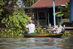 Folk som paddlar fartyget, i att sväva byn fotografering för bildbyråer