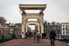 Folk som passerar den berömda träklaffbron Magere Brug med byggnader i bakgrunden i Amsterdam arkivfoto