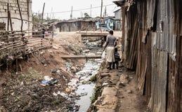Folk som promenerar en öppen avklopp i en slumkvarter i Afrika Arkivfoton