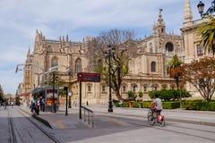 Folk som rider cykeln nära den Seville domkyrkan seville spain arkivbild