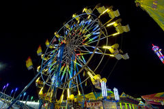 Folk som rider på en Ferris Wheel på natten Royaltyfri Foto