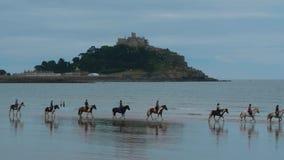 Folk som rider på hästar över stranden av Marazion i Cornwall arkivfilmer