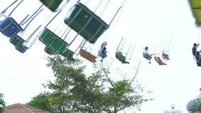 Folk som rider på kedjekaruselldragning i nöjesfält Lyckliga vänner som har gyckel på färgrik karusell i munterhet arkivfilmer