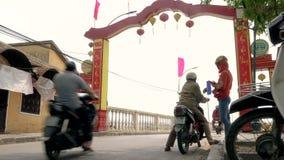 Folk som rider sparkcyklar på en bro över Thu Bon River och på daggatorna av Hoi An, Vietnam stock video
