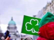 Folk som rymmer den gröna flaggan med treklöversymbol främst av det Belfast stadshuset Royaltyfria Foton
