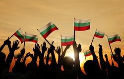 Folk som rymmer flaggan av Bulgarien i tillbaka Lit Arkivbild