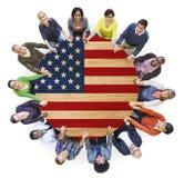 Folk som rymmer händer runt om tabellen med amerikanska flaggan Royaltyfri Fotografi