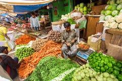 Folk som säljer grönsaker i en stor marknad med morötter, peppar, ärtor, tomater Arkivfoton
