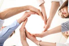 Folk som sätter deras händer i cirkel royaltyfria bilder