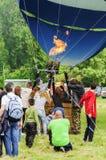 Folk som samlas runt om en ballong för varm luft Fotografering för Bildbyråer