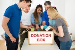 Folk som ser den inre donationasken Arkivbild