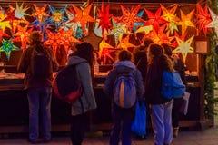 Folk som ser julstjärnagarneringar Arkivfoto