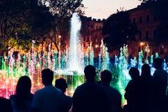 Folk som ser springbrunnen och ljus i aftonen Arkivbild