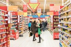 Folk som shoppar för mat i supermarketlagergång Arkivfoto