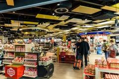 Folk som shoppar i tullfritt lager av Wien den internationella flygplatsen Arkivfoton