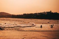 Folk som simmar och surfar på stranden på havet Royaltyfri Fotografi