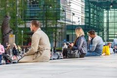 Folk som sitter på en låg vägg utanför Canary Wharf rörstation fotografering för bildbyråer
