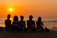 Folk som sitter på en strand som ser solnedgång Royaltyfria Bilder