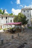 Folk som sitter på en terrass på en fyrkant i den lilla byn Sai royaltyfri fotografi