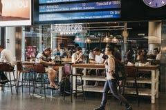 Folk som sitter på ett kafé som väntar på deras drev under depen arkivfoton