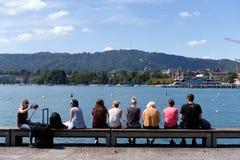 Folk som sitter på pir i Zurich Arkivbild