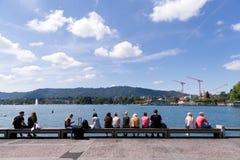 Folk som sitter på pir i Zurich Royaltyfri Foto