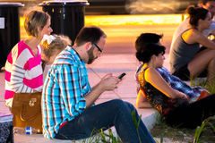 Folk som sitter på stads- vänta för trottoar Royaltyfri Bild