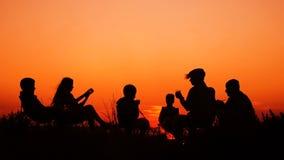 Folk som sitter på stranden med lägereld på solnedgången lager videofilmer