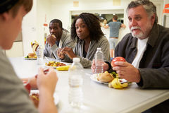 Folk som sitter på tabellen som äter mat i hemlöst skydd Arkivfoton