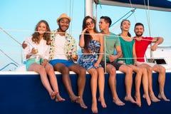Folk som sitter på yachtkanten royaltyfri foto