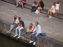 Folk som sitter vid kanalen i Ghent Royaltyfria Foton