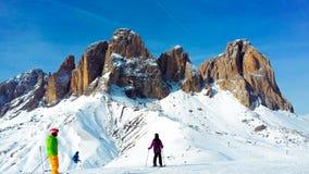 Folk som skidar i fjällängarna på en solig vinterdag royaltyfria foton