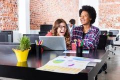 Folk som skrattar skämt för kollegor för bärbar dator för sammanträdekontorsskrivbord roligt royaltyfri bild