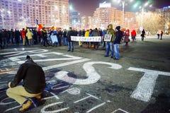 Folk som skriver meddelandet på betong på protesten, Bucharest, Rumänien Royaltyfri Bild