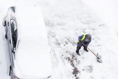 Folk som skyfflar snö nära bilen på parkering Snörensning efter ett tungt snöfall royaltyfri foto