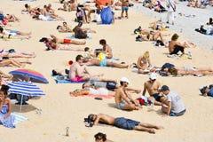 Folk som solbadar på stranden i Nice, Frankrike Arkivfoto