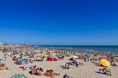 Folk som solbadar på den atlantiska stranden i Carcavelos, Portugal Arkivbilder