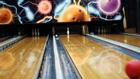 Folk som spelar bowlingen - färgrik boll som slår det bowla benet på bowlingbanan i en sportklubba medel Bowlingen stock video