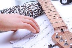 Folk som spelar gitarren med musikaliska ackord i mörkt rum arkivfoto