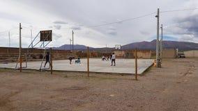 Folk som spelar i en basketdomstol i byn av villan Alota, Bolivia arkivfoto