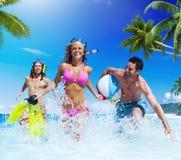 Folk som spelar på ett tropiskt strandnjutningbegrepp arkivfoton