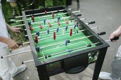 Folk som spelar tabellfotbollnärbild utomhus arkivfoton