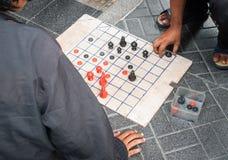Folk som spelar thailändskt schack på golvet Royaltyfri Bild