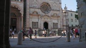 Folk som spenderar deras tid i Bergamo, nära den Cappella Colleoni kyrkan lager videofilmer