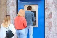 Folk som står i kö till bankomaten arkivbilder