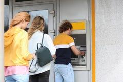 Folk som står i kö till bankomaten arkivfoton